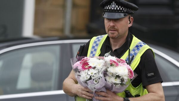 Полицейский несет цветы к месту убийства депутата Джо Кокс в Бирсталле близ Лидса