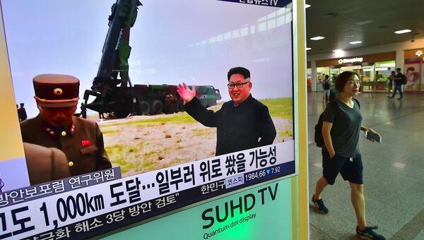 Женщина проходит мимо телевизионного экрана, транслирующего новости о последнем испытании ракет Мусудан в Северной Корее, 23 июня 2016