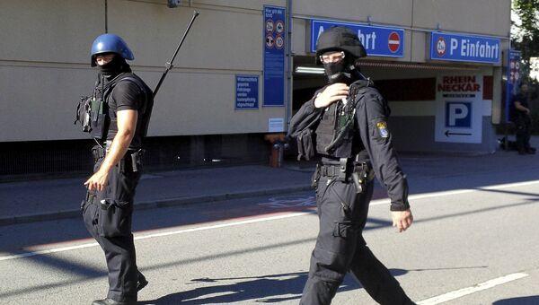 Полицейские у здания кинотеатра в немецком Фирнхайме, в котором произошла стрельба