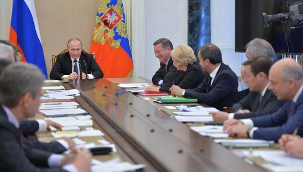 Президент России Владимир Путин (слева на дальнем плане) проводит совещание с членами кабинета министров РФ в Кремле