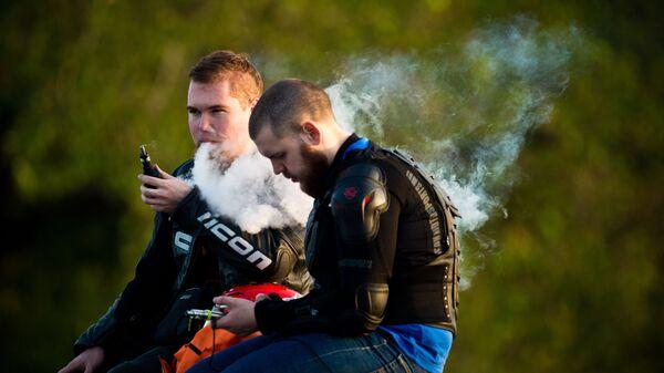 Молодые люди курят электронные сигареты