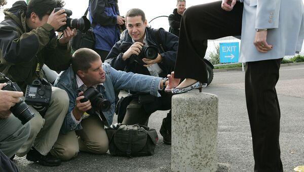 Фотографы делают снимки обуви британского политика Терезы Мэй