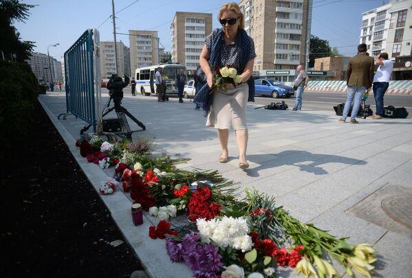 Женщина возлагает цветы у посольства Франции в Москве в память о погибших в результате террористических акта в Ницце