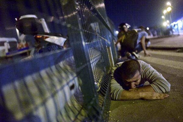 Люди прячутся от стрельбы на улице Стамбула. 16 июля 2016