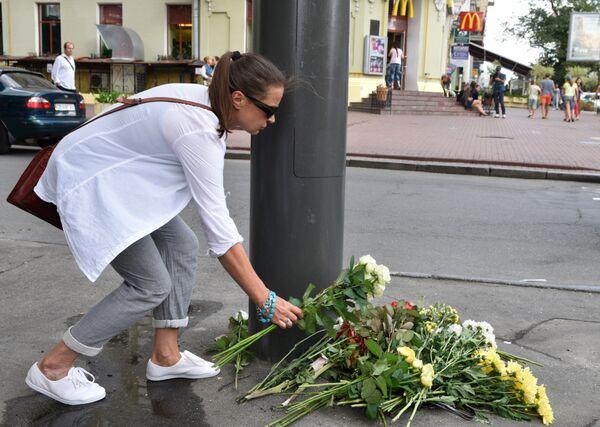 Женщина возлагает цветы к месту гибели журналиста Павла Шеремета