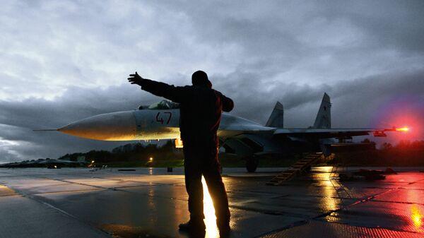 Военный техник дает отмашку на взлет истребителя Су-27