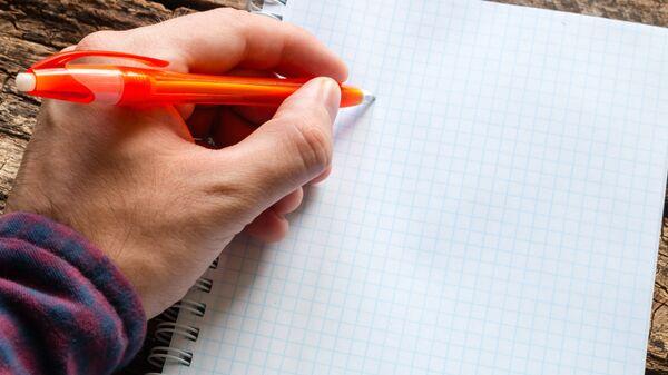 Мужчина пишет левой рукой