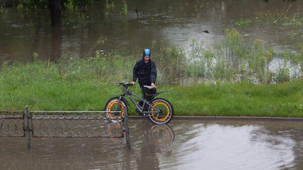 Велосипедист на затопленной набереной реки Яузы в Москве