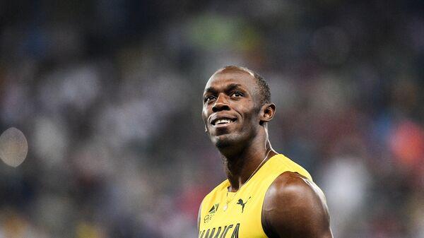 Усэйн Болт после финиша в финальном забеге на 100 м во время соревнований среди мужчин по легкой атлетике