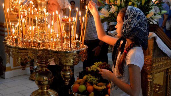 Верующие во время богослужения в честь праздника Преображения Господня в храме Успения Божией Матери