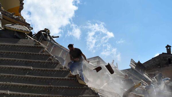Люди разбирают завалы в городе Аматриче, пострадавшем в результате землетрясения