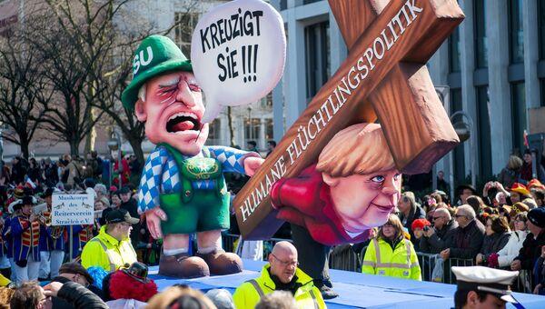 Карнавальная кукла, изображающая канцлера Ангелу Меркель, несущую крест с надписью: Гуманная миграционная политика, во время шествия в Дюссельдорфе, Германия. Архивное фото