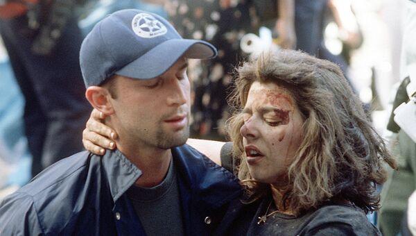 Доминик Гуаданоли помогает раненой женщине во время террористической атаки в Нью-Йорке. 11 сентября 2001 года