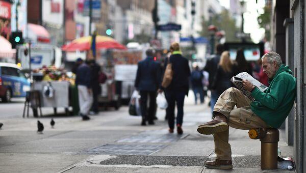Мужчина читает газету на улице в Нью-Йорке, США. Архивное фото