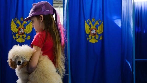 Девочка с собакой в единый день голосования на избирательном участке. Архивное фото