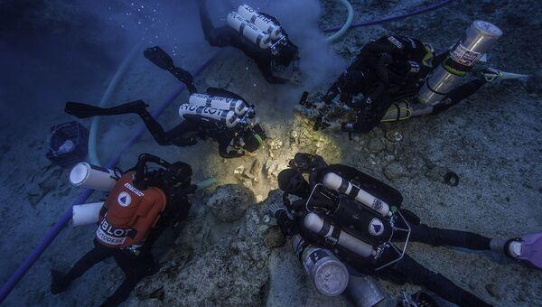 Водолазы извлекают останки человека из песков у остова древнего корабля