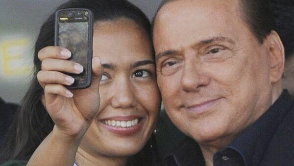 Премьер-министр Италии Сильвио Берлускони фотографируется со сторонницей во время встречи с членами партии Народ свободы