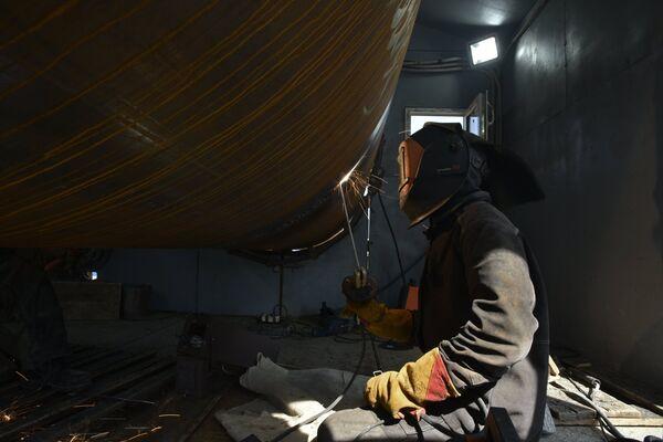 Рабочий сваривает сваю на строительной площадке моста через Керченский пролив в Крыму