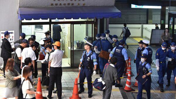 Японские полицейские у станции метро в Токио после сообщения об отравлении пассажиров
