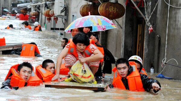 Спасатели эвакуируют жителей из зоны наводнения в Китае