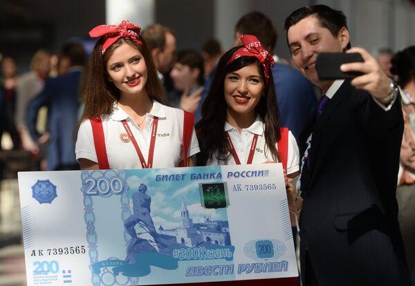 Мужчина фотографируется с образцом банкноты в 200 рублей на международном инвестиционном форуме Сочи 2016