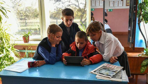Живущий в приемной семье Сергей (11 лет), Дима (9 лет), живущий в приёмной семье Максим (11 лет) и живущая в приёмной семье Аня (12 лет) (слева направо) на перемене в школе села Сенное в Брянской области