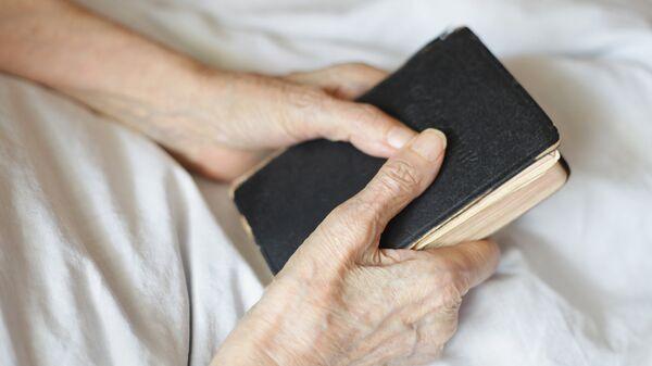 Библия в руках пожилого человека
