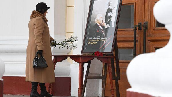 Женщина возлагает цветы к портрету актера Владимира Зельдина у театра Советской Армии в память о Владимире Зельдине