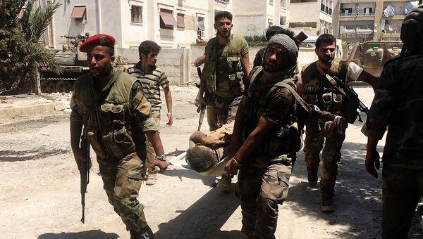 Бойцы сирийской армии выносят раненого на юго-западе Алеппо. Архивное фото