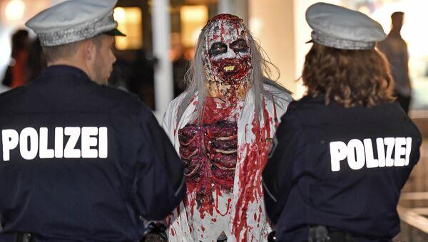 Участник парада на Хэллоуин в немецком городе Эссен общается с полицией