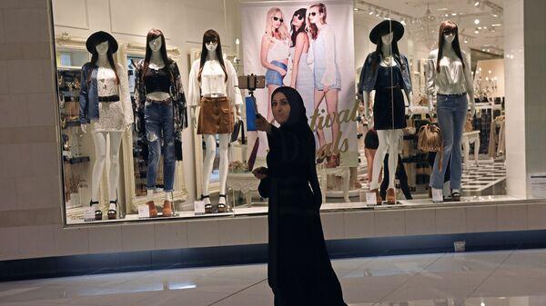 Посетительница фотографируется в дубайском торгово-развлекательном центре The Dubai Mall