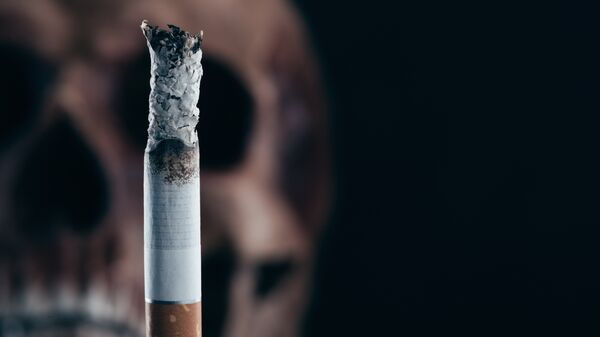Сигарета на фоне черепа. Архивное фото