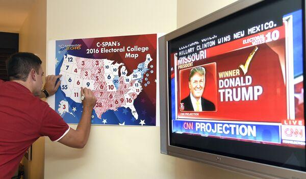 Мужчина следит за ходом голосования на выборах президента США