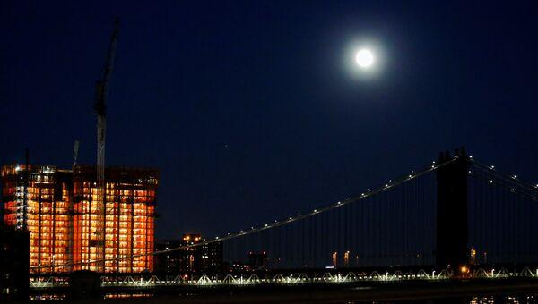 Луна над Манхэттенским мостом накануне суперлуния в Нью-Йорке, США. 13 ноября 2016