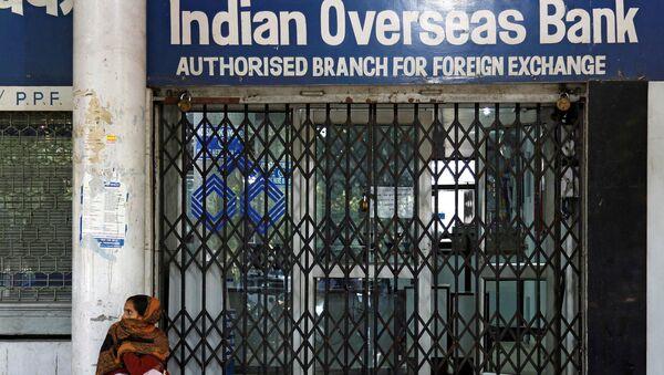 Женщина у закрытых дверей банка в Индии