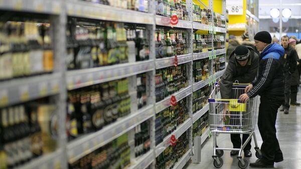 Покупатели выбирают пиво в отделе алкоголя. Архивное фото