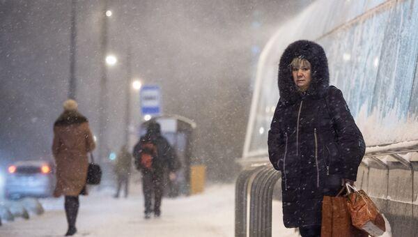 Прохожие у станции метро Новокосино в Москве во время снегопада