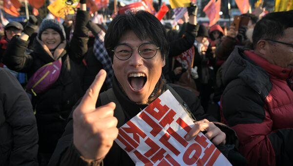 Протестующий радуется принятию решения об импичменте президенту Южной Кореи Пак Кын Хе у здания Национального собрания в Сеуле