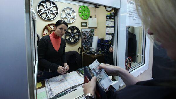 Автовладелец оплачивает услуги в кассе автосервиса. Архивное фото