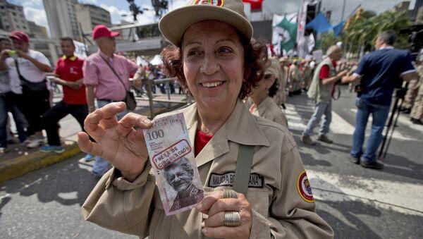 Образец венесуэльской банкноты в 100 боливаров с надписью из оборота в руках у полицейского