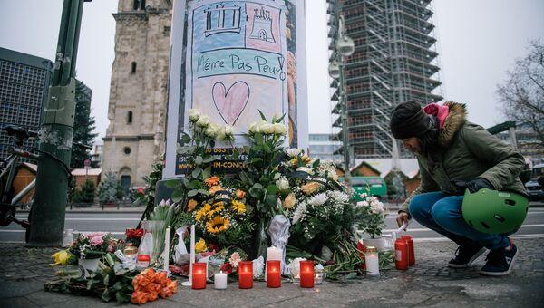 Девушка зажигает свечу недалеко от места теракта в Берлине