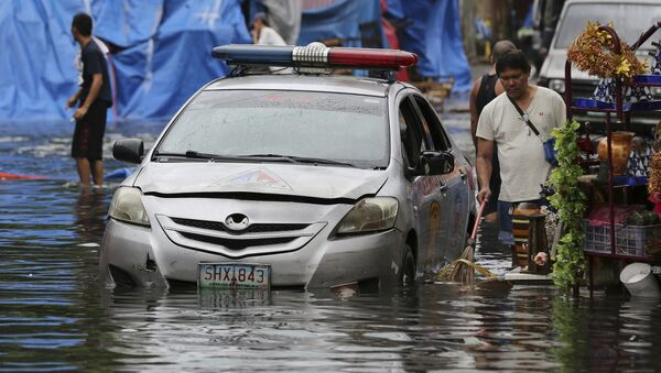 Полицейский автомобиль на улице, затопленной в результате тайфуна Нок-тен на Филиппинах