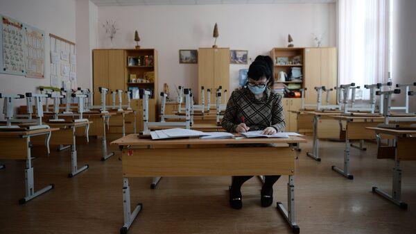 Учительница во время карантина по гриппу в средней общеобразовательной школе