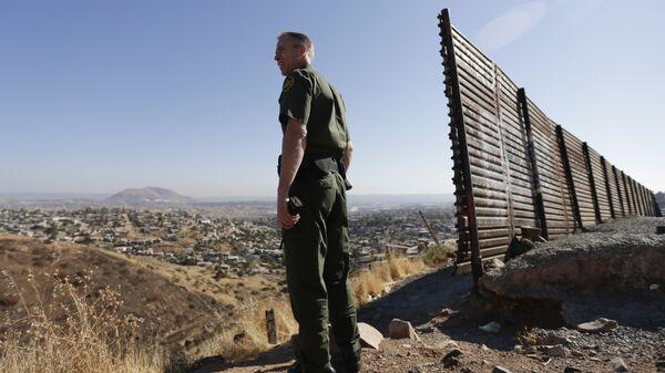 Сотрудник правоохранительных органов США у стены на границе