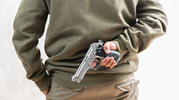 Мужчина с пистолетом за спиной