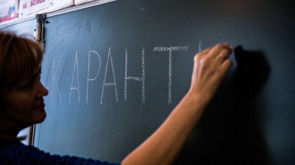 Учитель одной из школ Омска пишет на доске информацию о карантине