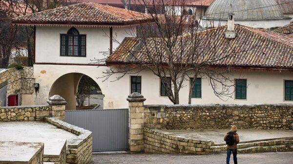 Прохожий идет по Историческому переулку вдоль Ханского дворца в Бахчисарае