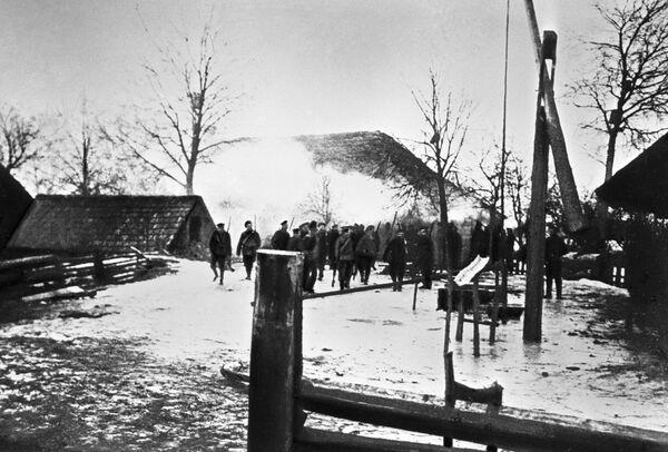 Солдаты входят на сожженный крестьянский двор, принадлежавший участнику восстания в Прибалтике в 1917 г.