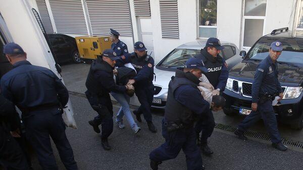 Сотрудники полиции Черногории ведут задержанных по подозрению в планировании вооруженных нападений в Подгорице