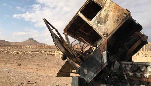 Кабина сгоревшего грузовика неподалеку от историко-архитектурного комплекса Древней Пальмиры в сирийской провинции Хомс